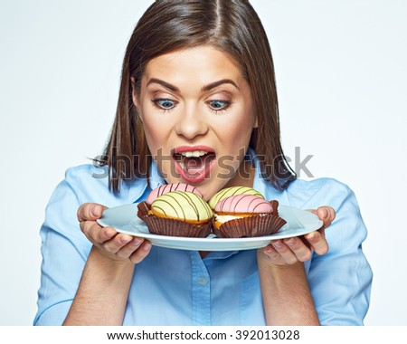 Woman holding plate with cookies and she wants to eat them. Happy girl with macaron french cookies. - stock photo