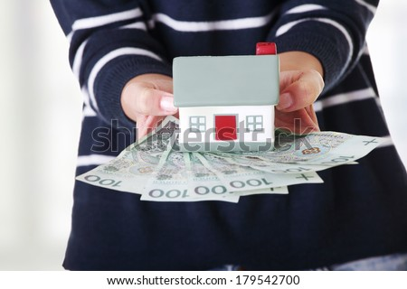 Woman holding PLN ( polish zloty ) bills and house model over white - real estate loan concept - stock photo