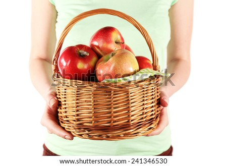Woman holding red apples in wicker basket on white background - stock photo