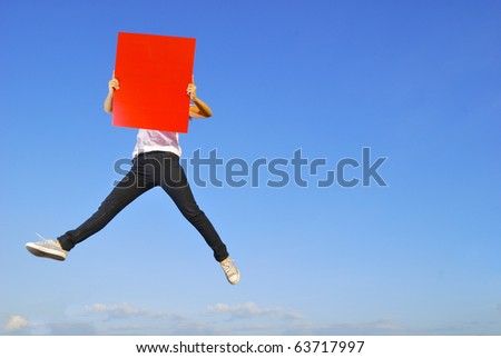 Woman holding red blank board jumping and blue sky - stock photo