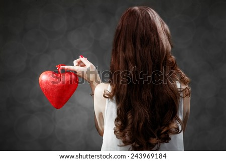 Woman holding red heart on grey background in studio, back view. Happy valentines greeting concept - stock photo