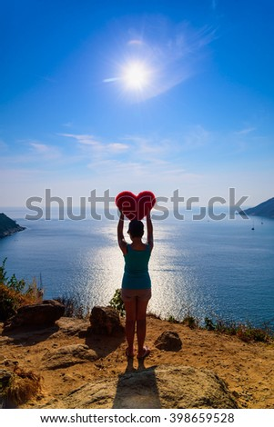 Woman holding red heart shaped pillow at viewpoint andaman sea in Phuket, Thailand.