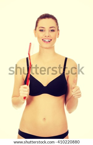 Woman holding red huge toothbrush - stock photo