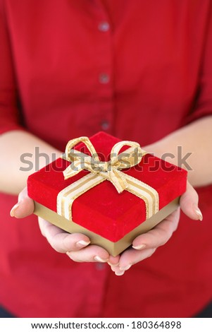 Woman holding red present  - stock photo
