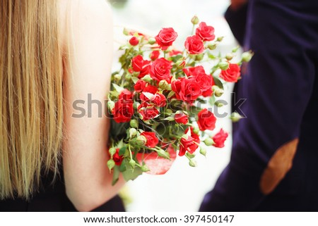 woman holding red roses bouquet