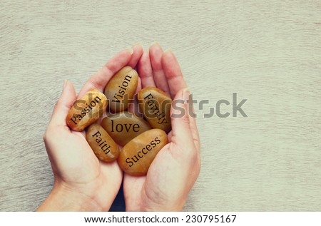 woman holding river stones with words written on them. love, success and family concept