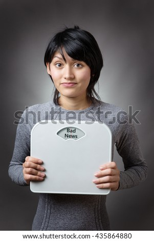 woman holding scales looking worried with the word bad news written on the weight dial - stock photo