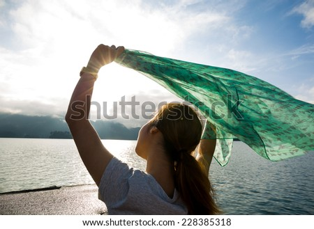 Woman holding scarf blowing behind.