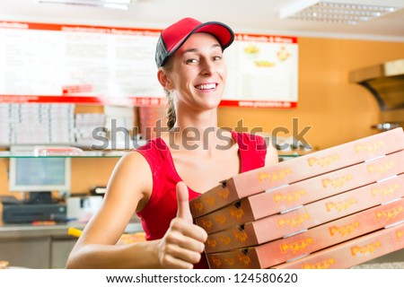 Woman holding several pizza boxes in hand and asking you to order pizza for delivery - stock photo