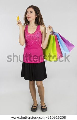 Woman holding shopping bags and a credit card daydreaming - stock photo