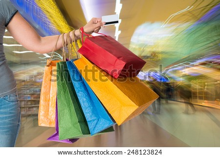 Woman holding shopping bags and credit card in the shopping mall