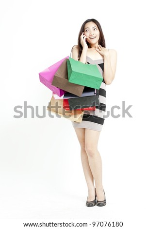 Woman holding shopping bags and talking on mobile phone against a white background