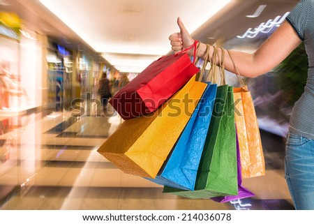 Woman holding shopping bags at shopping mall - stock photo