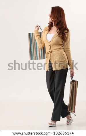 Woman holding shopping bags, smiling