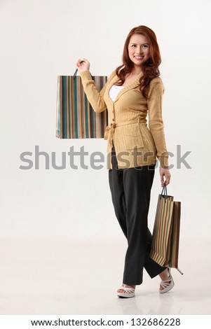 Woman holding shopping bags, smiling - stock photo