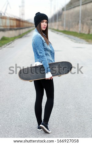Woman holding skateboard, looking back - stock photo
