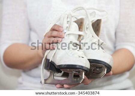 woman holding skates - stock photo