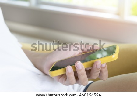 woman holding smart phone in cafe