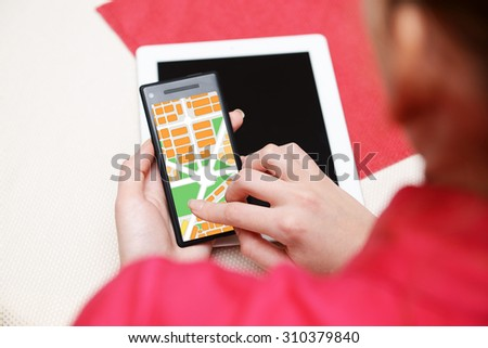 Woman holding smart phone with map gps navigation application