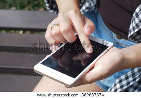 Woman holding smartphone - stock photo
