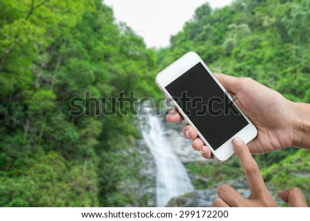 Woman holding smartphone against waterfall or mobile phone with blank mobile.Shallow depth of field. - stock photo