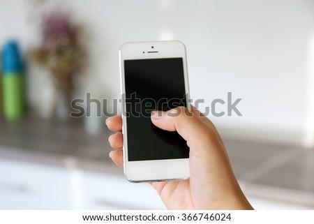 Woman holding smartphone indoors - stock photo