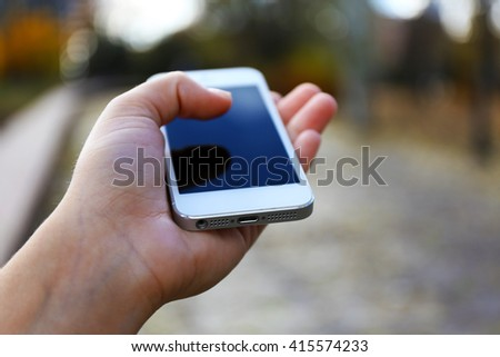 Woman holding smartphone outside