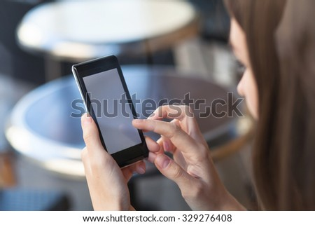 woman holding smartphone with empty screen in hands - stock photo
