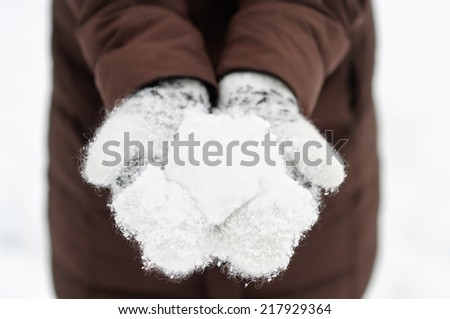Woman holding snowball in her hands - stock photo