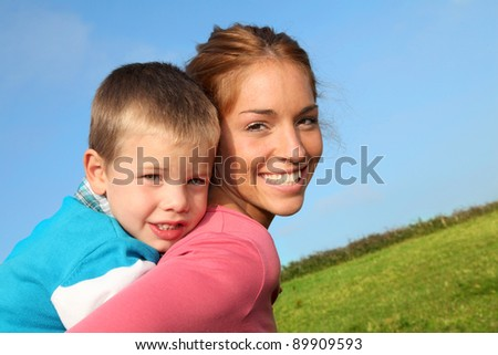 Woman holding son on her back - stock photo