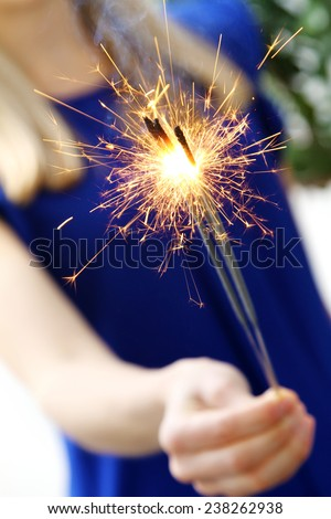 woman holding sparkler in her hand - stock photo