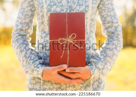 woman holding stacked books with ribbon. Education, reading, inspiration concept  - stock photo