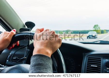 Woman holding steering wheel, drives the car
