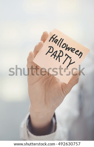 Woman holding sticky note with Halloween party text