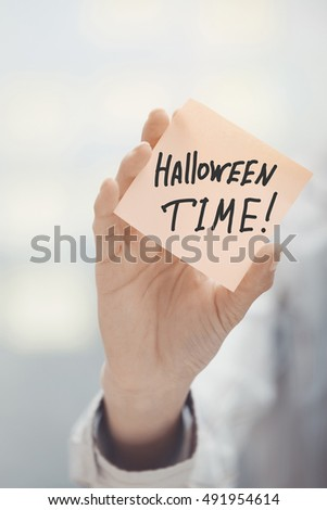 Woman holding sticky note with Halloween time text