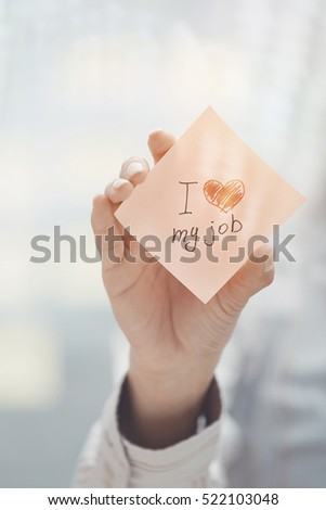 Woman holding sticky note with Love my job text