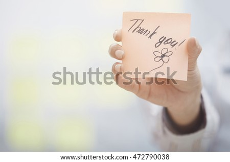 Woman holding sticky note with Thank you text