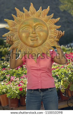 Woman Holding Sun's Sculpture In Front Of Face - stock photo