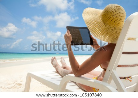 Woman holding tablet computer sitting on the beach in deck chair and taking sun bath - stock photo