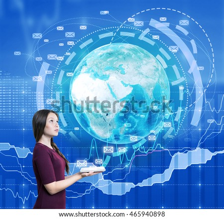 Woman holding tablet. Image of Earth and e-mail icons emerge from it. Charts on background. Concept of internet use during work and its benefit for business. Elements of this image furnished by NASA