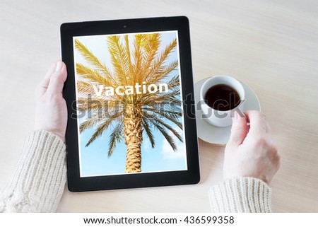 Woman holding tablet pc, drinking coffee and planning vacation, booking trip  - stock photo
