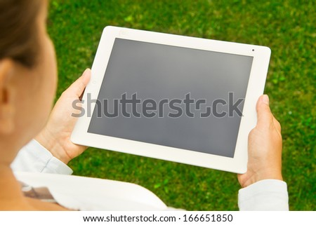woman holding tanbel PC on green grass lawn with copy space - stock photo