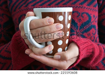 Woman holding tea cup - stock photo