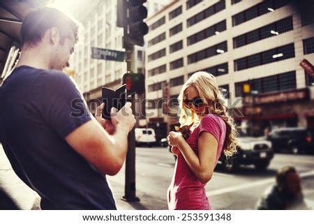woman holding teacup chihuahua in down town los angeles shot with lens flare and creative color filter - stock photo