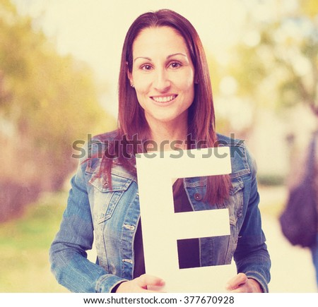 woman holding the E letter