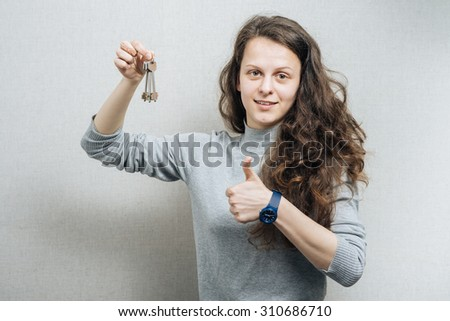 Woman holding the keys and showing thumb up. On a gray background. - stock photo