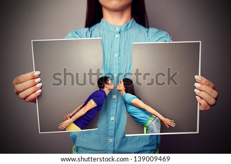 woman holding the lacerated photo of young kissing couple