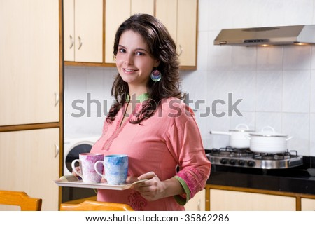 Woman holding tray with mugs