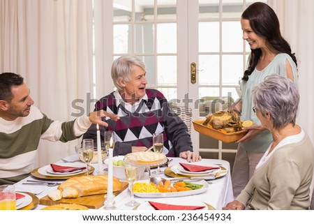 Woman holding turkey roast with family at christmas at home in the living room