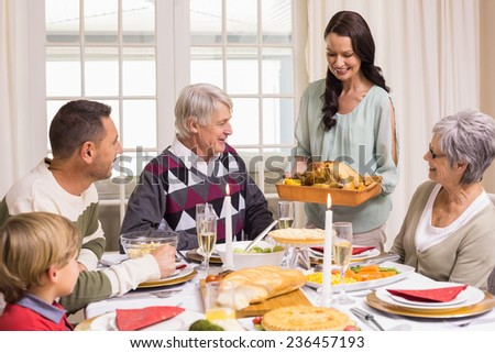 Woman holding turkey roast with family at dining table at home in the living room
